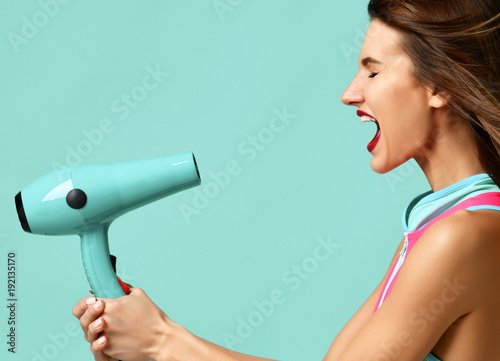 Happy young brunette woman with hair dryer on blue mint background Canvas Print