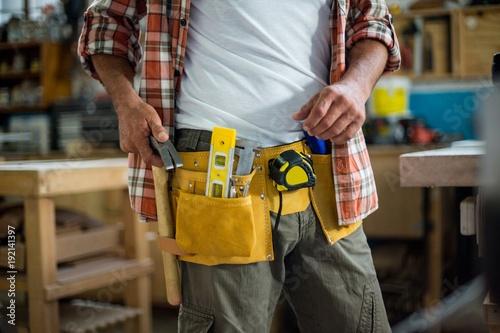 Carpenter removing hammer from tool belt