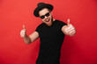canvas print picture - Image of excited young guy wearing black sunglasses and hat smiling and pointing fingers on camera meaning hey you, isolated over red wall