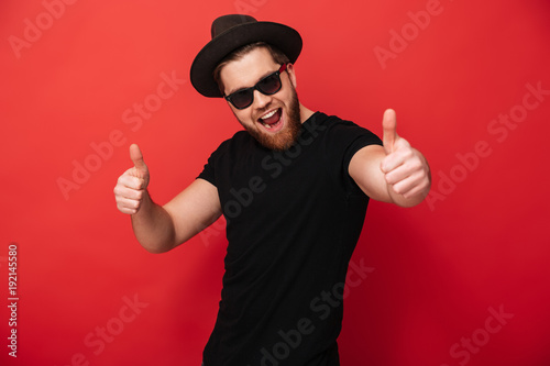 Valokuva  Image of excited young guy wearing black sunglasses and hat smiling and pointing