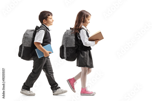 Photo  Full length profile shot a schoolboy and a schoolgirl with backpacks and books w