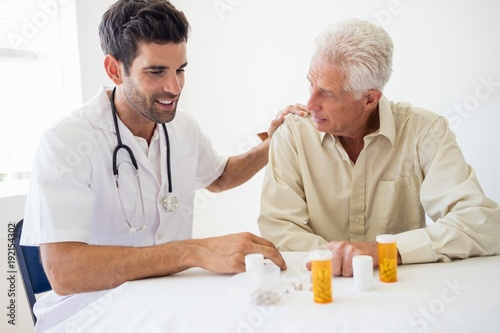 Nurse giving medicine to senior man
