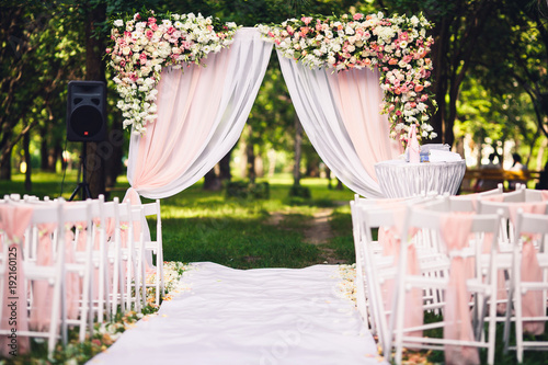 Obraz Decor wedding ceremony in the summer in the park: an arch, chairs, flowers, path. - fototapety do salonu