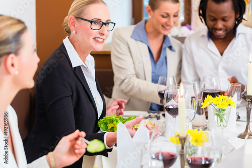 Photo Group of men and women at business lunch in restaurant eating and drinking
