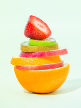 Stack Of Different Fruit Slices On Sofe Green Background, Concept For Health Care, Fruit Punch