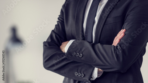 Torso of a businessman standing with folded arms Canvas Print
