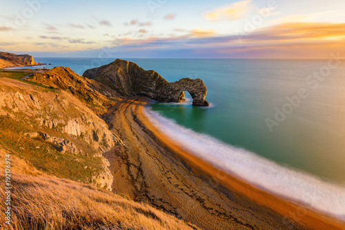Montage in der Fensternische Kuste Gorgeous golden light at the famous Durdle Door on the Jurassic Coast, Dorset, UK.