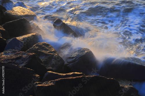 Poster Marron chocolat Blurred sea wave crashing over rocks at Sunrise on The Cobb in Lyme Regis, Dorset