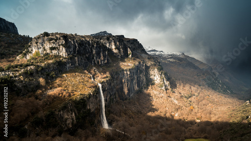 View of waterfall flowing through mountains