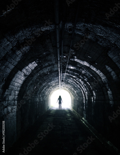 Silhouette standing in dark tunnel