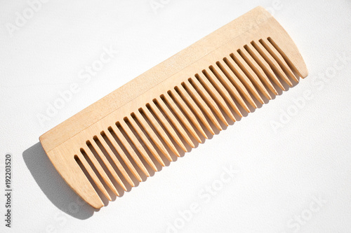 Thin comb of light wood on a white background Fototapeta