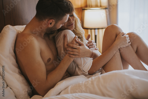 Lovely couple hugging on their bed at home Wallpaper Mural