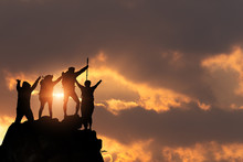 Businessman And Women Group Hike On The Peak Of Silhouette Rocks Mountain At Sunset, Success, Winner And Leader Concept .