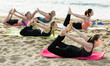 Positive young women training yoga positions on beach