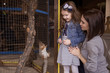 Mom and daughter in the contact zoo feed the red squirrel in the cage. A happy family. Life style.