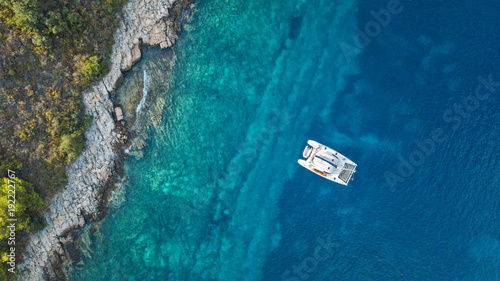Fotografiet Aerial view of anchoring catamaran next to island.
