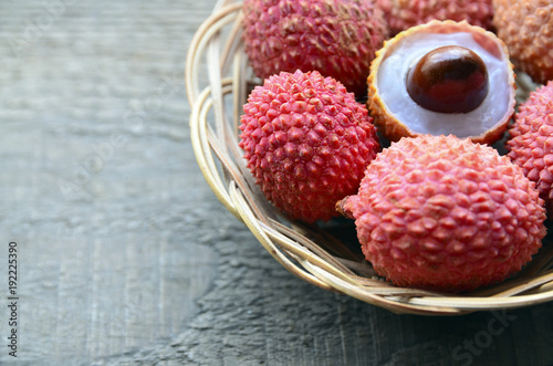 Fresh organic lychees in a basket on old wooden background.Exotic tropical lychee fruits.Raw diet or vegan food concept.Selective focus.