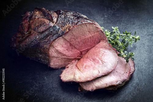 Photo Barbecue dry aged haunch of venison with herbs as close-up on a board