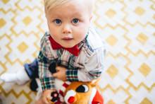 Little Boy Sitting On A Rug Lo...