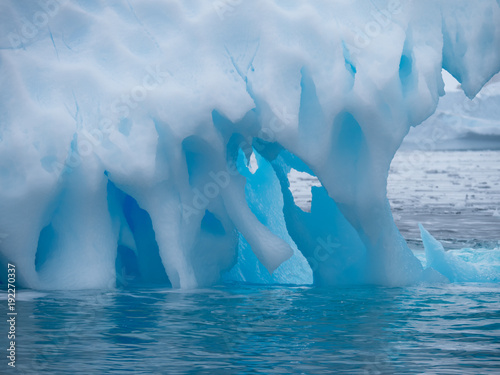 Tuinposter Antarctica Close Up of a light and medium blue iceberg with divots, holes and spikes. It is in the Southern Ocean in Antarctica.