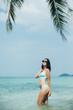 slim girl in bikini and sunglasses at tropical sea resort