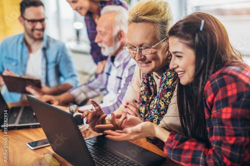 Fotografie, Obraz  Young volunteers help senior people on the computer