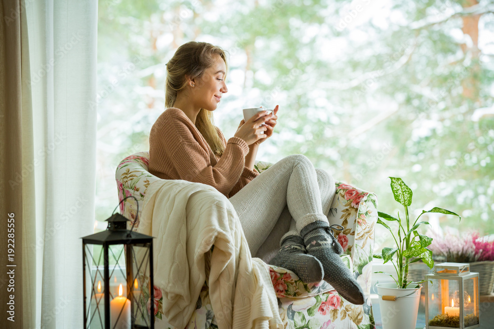 Fototapety, obrazy: Young woman sitting home in a chair by the window with cup of hot coffee wearing knitted warm sweater. Cozy room decorated with lanterns and candles. Scenic view of pine trees in snow in window