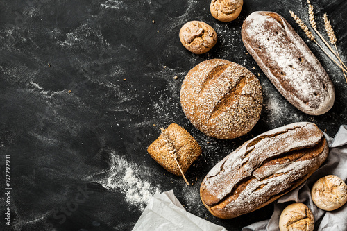 Fototapeta Bakery - rustic crusty loaves of bread and buns on black