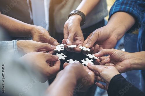 Closeup image of many people hands holding a jigsaw puzzle in circle together Canvas-taulu