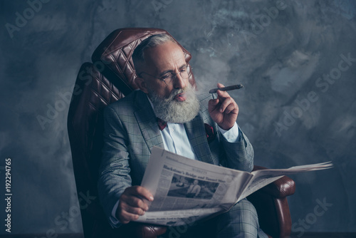 Fotografía  Portrait of brutal harsh old man in tuxedo holding, reading, looking at newspape