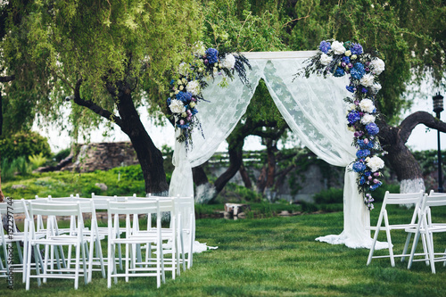 Fotografía  The wedding arch is decorated with fabric and flowers, chairs for guests