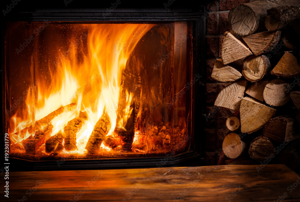 Fototapety, obrazy: Old wooden table and fireplace with warm fire at the background.