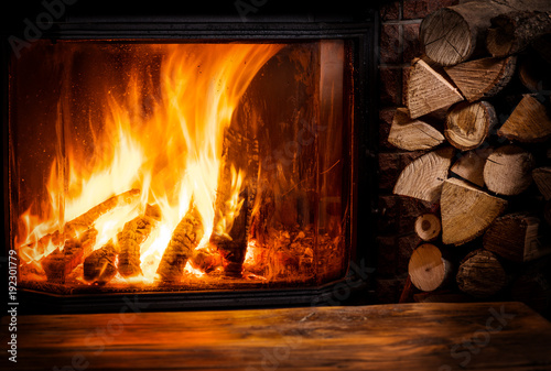 Obraz Old wooden table and fireplace with warm fire at the background. - fototapety do salonu