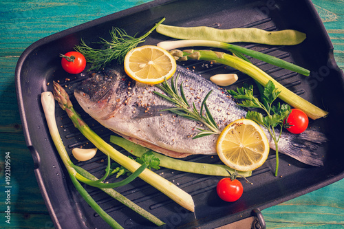 Preparing fresh sea bream with vegetables in a frying pan