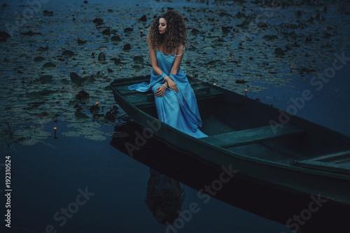Spoed Foto op Canvas Gondolas Model wearing blue dress is posing in a boat on the water