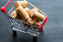Used Red Vine Corks In Shopping Cart On Wooden Black Backgroiund. Shopping Alcohol Concept With Copy Space