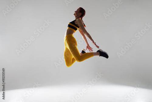 Fotografiet  woman in sportswear jumping