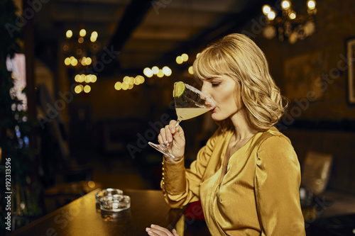 Elegant woman drinking cocktail in a bar