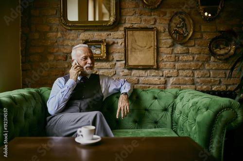 Senior man sitting on sofa and talking on phone