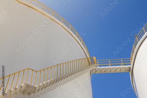 Photo  white fuel tanks against blue sky, white steel petroleum silo