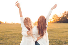 Two Pretty Girls Raised Their Hands On A Field At Sunset.