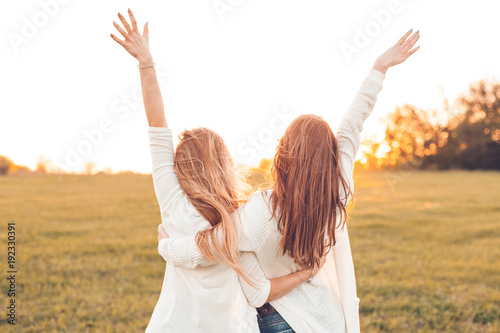 Fototapeta Two pretty girls raised their hands on a field at sunset.