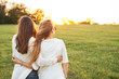 canvas print picture Two young women are looking forward tothe sunset on the green field.