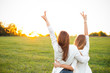 canvas print picture Two women in white sweaters are looking on the sunset. Best friends