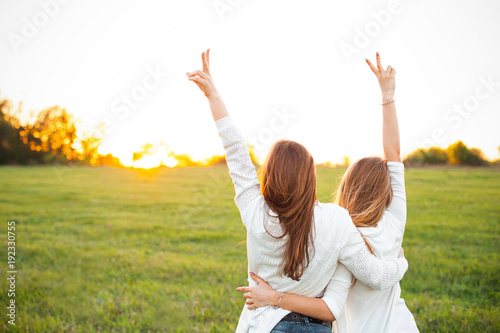 Two women in white sweaters are looking on the sunset Fototapet