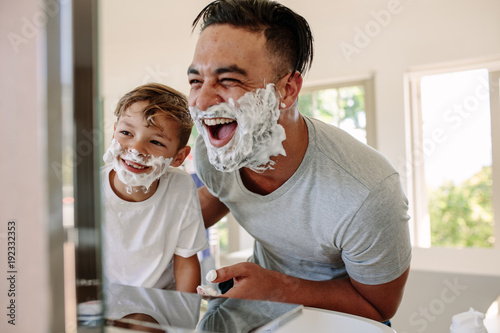 Happy father and son having fun while shaving