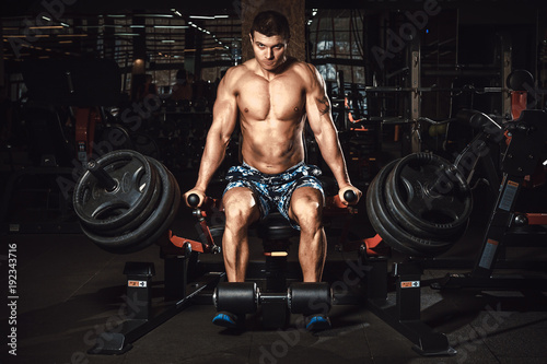 Man doing exercise for triceps muscles in lift machine in gym