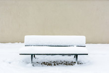 Front View Of A Public Wooden Bench Covered In Snow In Front Of A Wall In The Trocadero Garden In Paris.