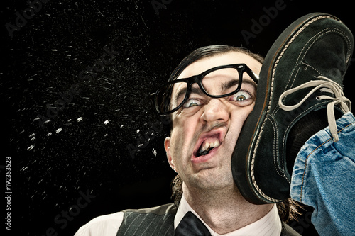 Fotografía  elegant nerd with glasses hit by kick on black background
