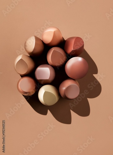 Poster Brown lipstick pieces on beige background